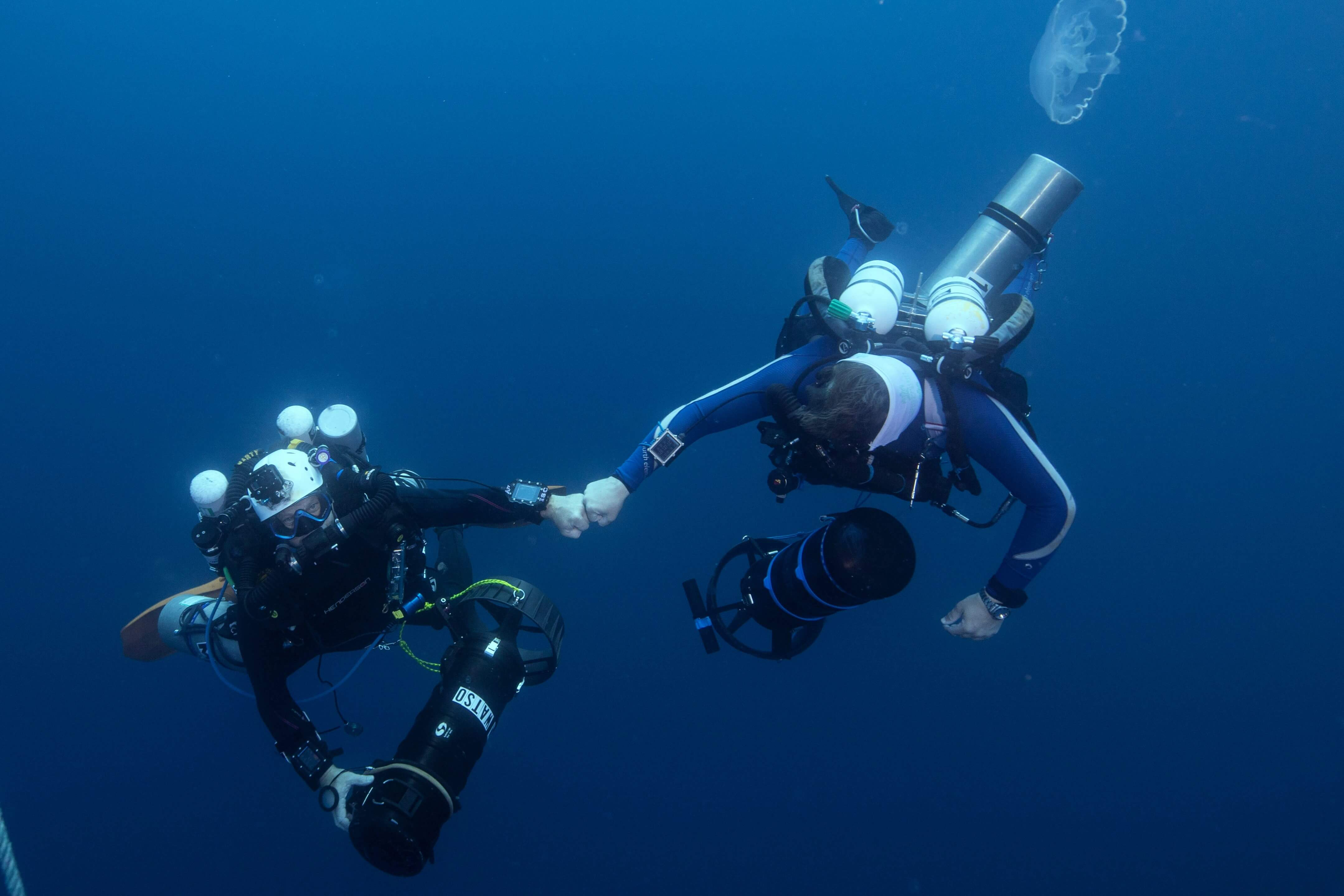 Divers share a fist bump during a Mote-led expedition to explore a blue hole in the Gulf of Mexico. Credit: Kristin Paterakis