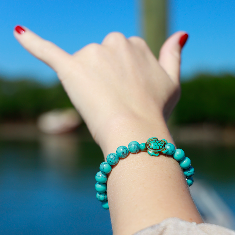 Hand with a turquoise-colord sea turtle bracelet from Ocean & Company