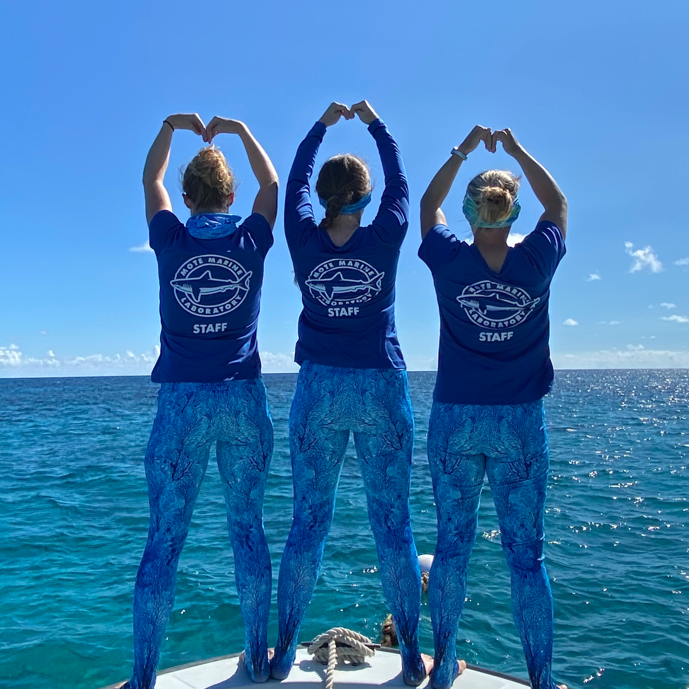Three Mote staff members stand on a boat and raise their arms to make a heart shape.