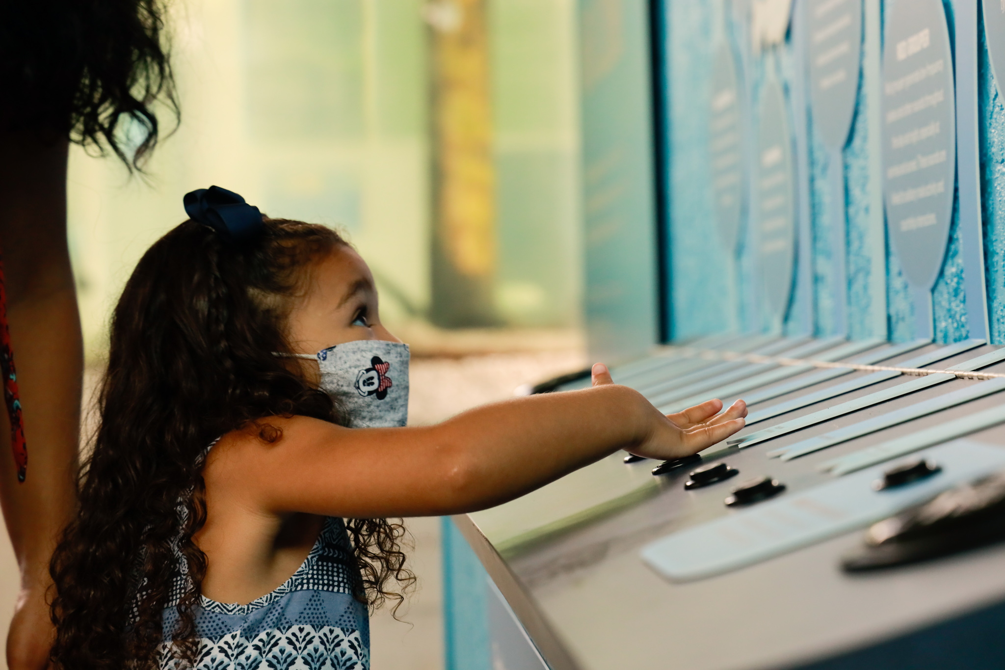 A girl wearing a mask pushes a button on an interactive exhibit at Mote Aquarium