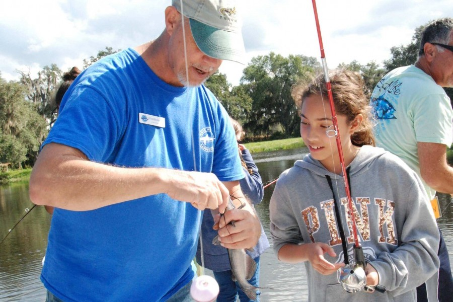 Mote's Dr. Nathan Brennan shows a Brentwood Elementary student how to fish. Credit: Mote Marine Laboratory