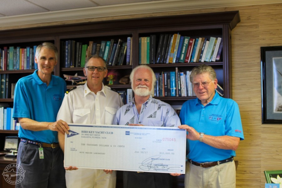 Dr. Michael P. Crosby receives donation check from Jon Turner, Bob Williams and Bill Jacobs of Bird Key Yacht Club.