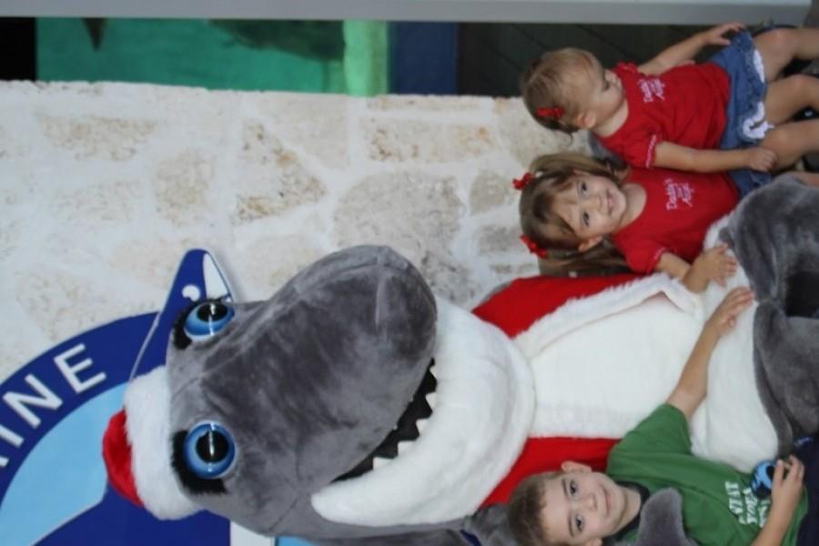 Photo: Santa Jaws poses with James, Karlee and Lindsey Farah at Mote Aquarium. Credit Mote Marine Laboratory