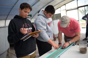 At one of the three stations students discussed sustainability and economics as they weighed juvenile fish for health assessments.