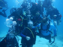 Dr. Michael P. Crosby, President & CEO of Mote Marine Laboratory poses underwater with SCUBAnauts International members in celebration of the successful planting of 250 coral fragments near Looe Key reef in the Florida Keys on Monday, July 20, 2015.